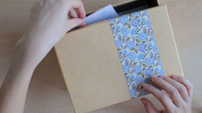 Girl`s hands put a greeting card into a gift box and close it gently. Note `For you` and heart on the gift card stock video