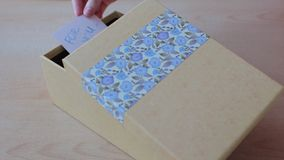 Girl`s hands put a greeting card into present box and close the box stock video