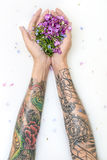 Girl`s hands with tattoos and flowers. Female arms with colorful tattoos on the surface of milk with flower petals. She holds multicolored flowers on her palms stock photo