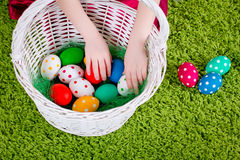 Girl's hands are touching  Easter eggs in a basket Royalty Free Stock Images