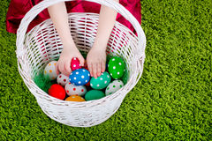Girl's hands are touching  Easter eggs in a basket Royalty Free Stock Photography