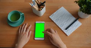 Girl`s hands touching green chroma-key smartphone screen on wooden table. Girl`s hands are touching green chroma-key smartphone screen on wooden table in modern stock video footage