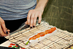 Girl`s hands twisting rolls and sushi close-up Royalty Free Stock Photography