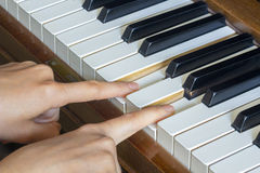 Girl's hands two fingers holding pressed  keys on a piano Royalty Free Stock Photography