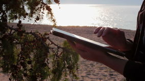 Girl's hands using a tablet pc on the Baikal beach. Close-up stock footage