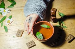 Girl& x27;s hands, runes and hot mint tea Royalty Free Stock Images