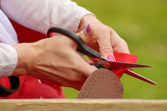 The girl`s hemming shoes. The The woman torn shoes,and she decided to repair it.girl`s hemming shoes Stock Image