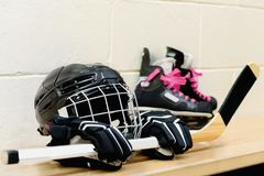 Girl`s hockey gear: helmet, gloves, sticks, skates with pink laces. All equipment are on bench stock photography