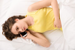 Girl's intimacy secret. Young worried girl talking on phone about her intimacy secret Royalty Free Stock Photography