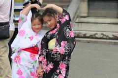 Girl`s kimonos post and smile for photo within Fushimi Inari shr Royalty Free Stock Photo