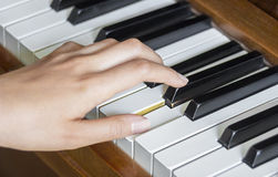 Girl's left hand holding pressed  keys on a piano Royalty Free Stock Image