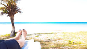 Girl`s leg lay on white armchair in the beach Royalty Free Stock Photo