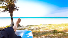 Girl`s leg lay on white armchair in the beach Stock Images