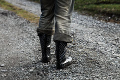 Girl's leg in wellington boots on gravel road Royalty Free Stock Photography