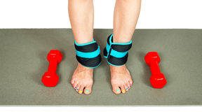 Girl's legs with ankle weights and dumbbells, isolated Stock Photo