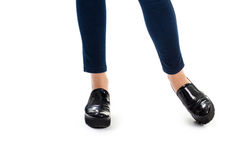 Girl's legs in black shoes. Footwear on thick sole. Glossy leather of high quality. Durable and stylish shoes Royalty Free Stock Images