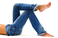 Girl's legs in blue jeans. Girl's legs in a blue jeans over white Royalty Free Stock Photos