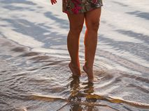 Girl`s legs in the river at sunset stock images