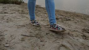 Girl`s legs in jeans and shoes go to beach, girl goes to lake in evening. Close-up stock photo