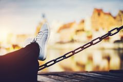 Girl`s legs leaning on a chain, a river and old buildings in background stock photos
