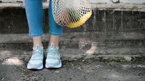 Girl`s legs reusable mesh string knitted shopping bag with fruits and vegetables, moving. Girl`s legs reusable mesh string knitted shopping bag with fruits and stock video footage