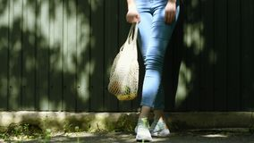 Girl`s legs reusable mesh string knitted shopping bag with fruits and vegetables, moving. Girl`s legs reusable mesh string knitted shopping bag with fruits and stock video