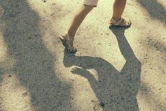 Girl's legs running on ground Stock Images