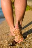 Girl's legs on sand beach Stock Photo