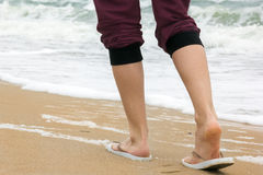 The girl`s legs walking on the beach Stock Photography