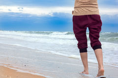 The girl`s legs walking on the beach Stock Images