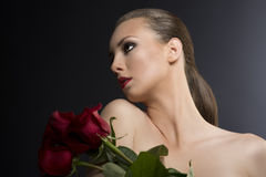 Girl's low key  portrait with roses Stock Photo