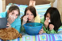 Girl's Movie Night. Three young teens laying in bed crying over sad movies in their pajamas