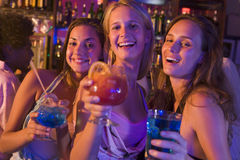 Girl's Night Out. Three girls holding alcoholic drinks in a bar and smiling cheerfully Royalty Free Stock Photography