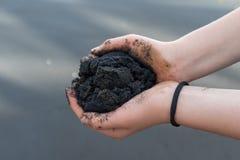 Girl`s palms full of volcanic black lava sand Royalty Free Stock Photo