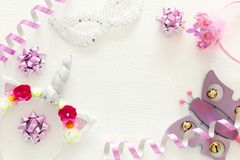 girl& x27;s party concept. unicorn head decoration, pink wand, mask and toy over white wooden background. stock photo