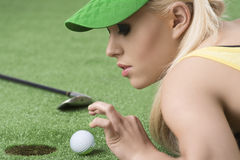 Girl's playing with golf ball, she looks the ball. Pretty blonde girl is lying on the grass and playing with golf ball, she is in profile and looks the ball Stock Images