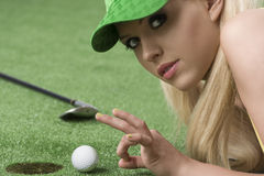 Girl's playing with golf ball looks in to the lens. Pretty blonde girl is lying on the grass and playing with golf ball, she is turned of three quarters and Stock Photo