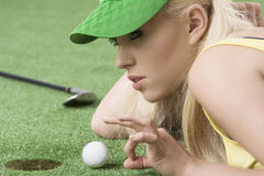 Girl's playing with golf ball, she is in profile. Pretty blonde girl is lying on the grass and playing with golf ball, she is about to hits the ball with left Stock Image