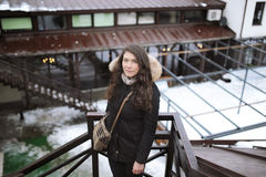 The girl`s portrait in a black short fur coat who stands behind a handrail and looks in a distance in the winter.  Royalty Free Stock Image