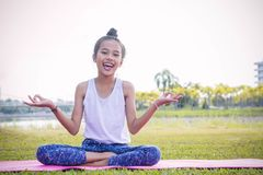 Girl`s practicing yoga in the park Strengthens concentration an. D health , Yoga for kid have fun Meditation activities for children royalty free stock images