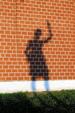Girl's shadow on a red brick wall. Girl's shadow with the raised hand on a red brick wall Royalty Free Stock Photography