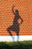 Girl's shadow on a red brick wall. Girl's shadow with the raised hand and a leg on a red brick wall Royalty Free Stock Images