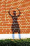 Girl's shadow on a red brick wall. Girl's shadow with the raised hands on a red brick wall Royalty Free Stock Photography