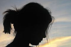 Girl's Silhouette against Dreamy Sunset Sky Stock Images