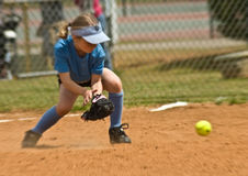 Girl's Softball. A young girl making a play for a ball during a softball game Stock Photos