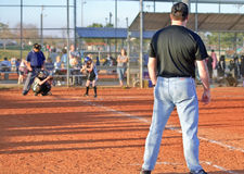 Girl's Softball / At Bat. Action at home plate during a game, batter, catcher, and umpire, view from behind the first base coach.  9 and 10 year old girls ASA Royalty Free Stock Images