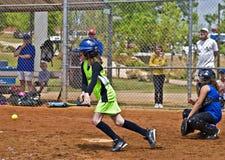Girl's Softball Making a Hit. CUMMING, GA, USA - APRIL 23: Young baseball player ready to run to base after a hit.  Forsyth County, Cumming GA, April 23, 2011 Royalty Free Stock Image