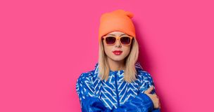 Girl in 90s sports jacket and hat with sunglasses stock image