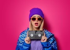 Girl in 90s sports jacket and VHS cassette royalty free stock image