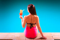 Girl s in swimsuit at poolside with cocktail glass back view. Stock Images